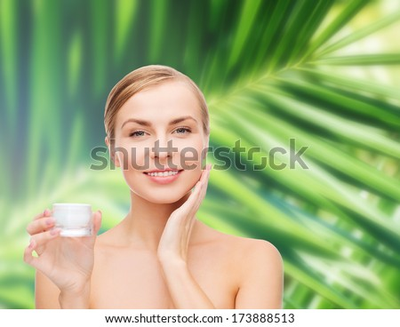 cosmetics, health and beauty concept - beautiful woman applying cream on her skin - stock photo