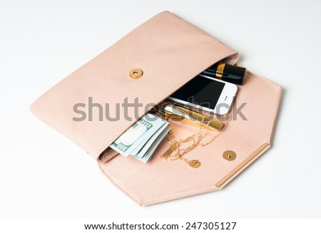 Cosmetics, jewelry, money and smartphone in an open beige woman's clutch handbag on a white background. - stock photo