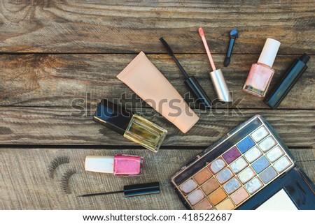 Cosmetics: mascara, eyeliner, false eyelashes, concealer, nail polish, perfume, lip gloss and eye shadow on wooden background. Toned image.  - stock photo