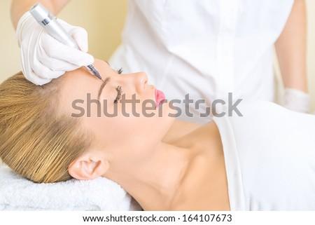 Cosmetologist applying permanent make up on eyebrows - stock photo