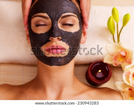 Cosmetologist doing massage on the woman's face  in sap salon. Female with scrub cosmetic mask on face.  - stock photo