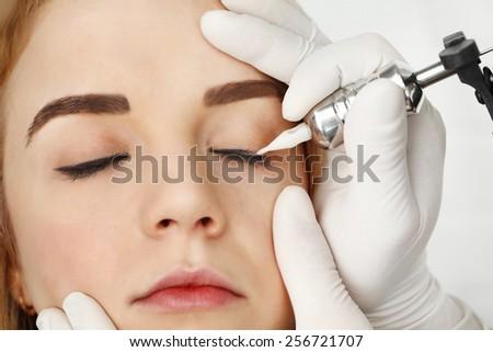 Cosmetologist making permanent makeup, close up - stock photo