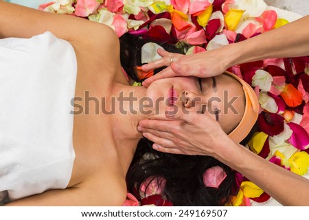 Cosmetology spa facial. Beautiful brunette in a spa salon. Girl lying on petals of roses in a beauty salon.Cosmetology, beautician, beautiful background - concept of a facial care.  - stock photo
