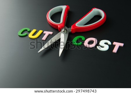 Cost cutting concept illustrated with pair of scissors between the words cut and cost on black background - stock photo