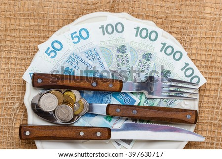 Cost of living, price of eating food budget concept. Polish money on kitchen table, plate with banknotes cutlery - stock photo