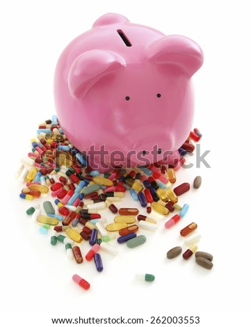 Cost of Medicine - Piggy Bank on White Background with pills - stock photo