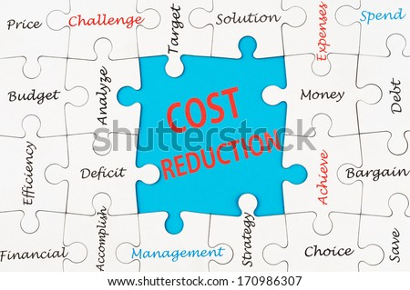 Cost reduction concept word cloud on group of jigsaw puzzle - stock photo