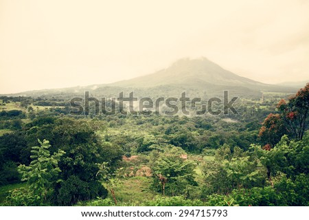 Costa Rica raw landscape. Arenal volcano and lake area. Vacation, outdoors, travel, nature concept. Vintage colors post processed. - stock photo