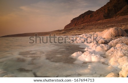Costal view of Dead sea in Jordan with sunset scenary behind - stock photo