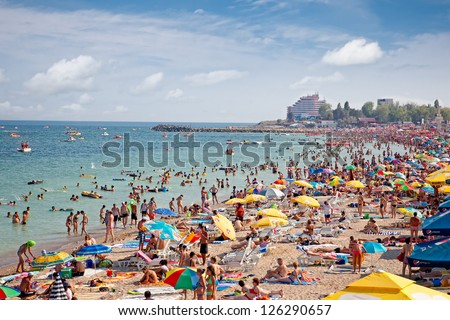 COSTINESTI, ROMANIA - AUGUST 6: Crowded beach with tourists in summer on August 6, 2012 in Costinesti, Romania. Costinesti is a famous summer destination for hundred of thousands of tourists a year. - stock photo