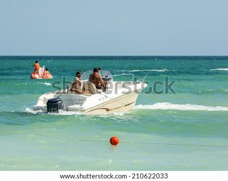 COSTINESTI, ROMANIA - JULY 28, 2014: People Riding Motor Boat On The Black Sea Beach In Costinesti Holiday Resort. - stock photo