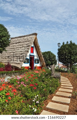 Cosy chalet with a triangular thatched roof. Before the house - garden with beautiful flower beds. Madeira Island, the city Santana - stock photo