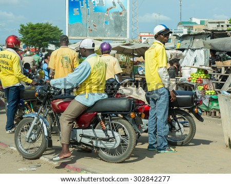 Cotonou, Benin: May 26: A man rides a Motorcycle taxi, the most common means of hired transportation in the city, on May 26, 2015 in Cotonou, Benin. - stock photo