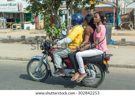 Cotonou, Benin: May 26: Two womnn ride a hired Motorcycle taxi, the most common means of hired transportation in the city, on May 26, 2015 in Cotonou, Benin. - stock photo