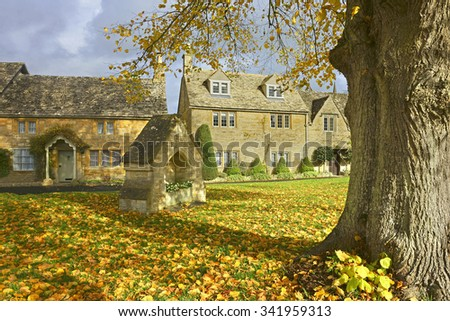 Cotswold cottages near the River Eye on a beautiful Autumn day in the popular tourist destination of Lower Slaughter, The Cotswolds, Gloucestershire, U K - stock photo