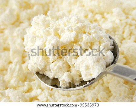 Cottage cheese clods and spoon. Macro image. - stock photo