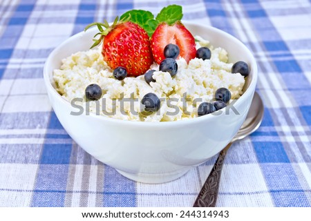 Cottage cheese in a white bowl with strawberries, blueberries and mint, a spoon against a background of blue linen tablecloth - stock photo