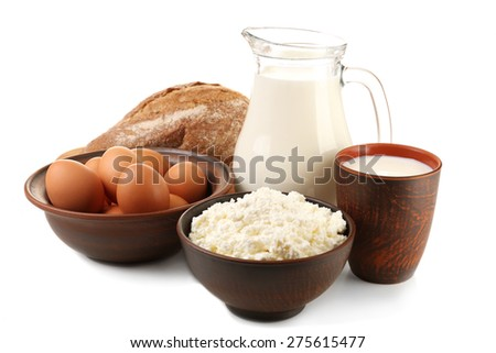 Cottage cheese, milk and eggs with loaf of bread isolated on white - stock photo