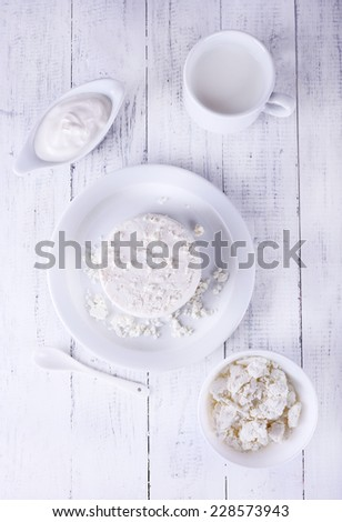 Cottage cheese on plate and in bowl, cup of milk and cream in saucer boat on wooden background - stock photo