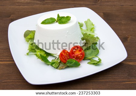 Cottage cheese on the plate on wooden table - stock photo