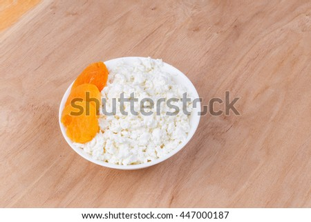 cottage cheese with dried apricots on a wooden table - stock photo