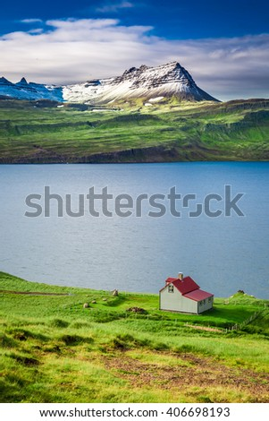 Cottage in the mountains above the fjord, Iceland - stock photo