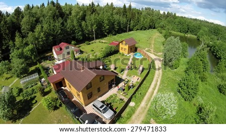 Cottage settlement with family get rest on yard at summer sunny day. Aerial view - stock photo