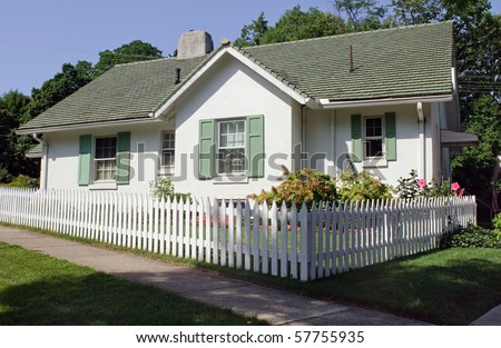 Cottage with Picket Fence - stock photo