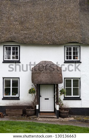 Cottage with thatch roof - stock photo