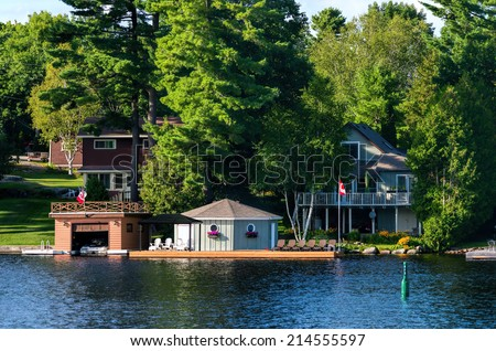 Cottages and boathouses on a lake - stock photo