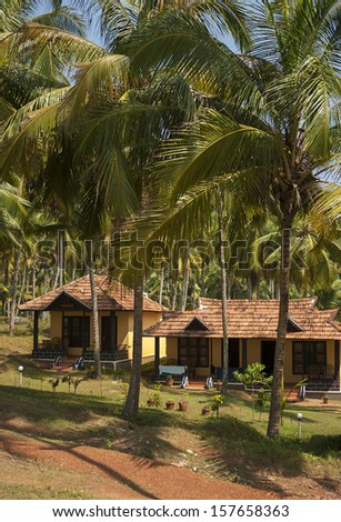 Cottages in a palm grove. Varkala, Kerala, India. - stock photo