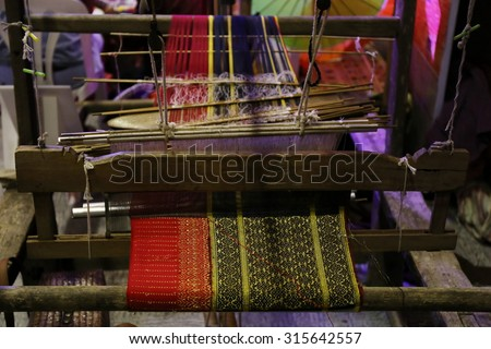 cotton on the manual wood loom in Asian traditional culture and woman lifestyle ,Weaving shuttle on the warp, Weaving loom and shuttle on the warp. fashion fabric factory and business in Thailand.hand - stock photo