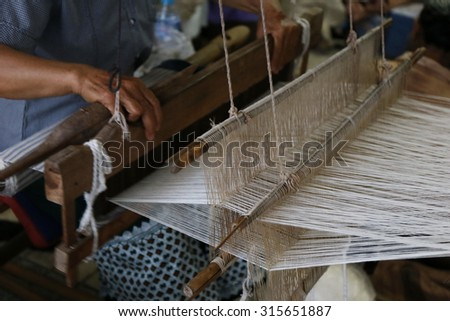 cotton on the manual wood loom in Asian traditional culture and woman lifestyle ,Weaving shuttle on the warp, Weaving loom and shuttle on the warp. fashion fabric factory and business in Thailand. - stock photo