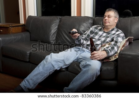 Couch potato watching TV and drinking beer - stock photo