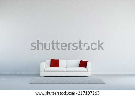 Couch with pillows and a carpet in front of a concrete wall - stock photo