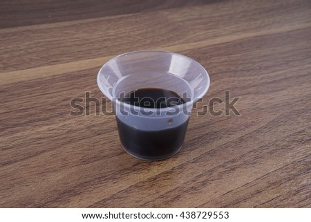 Cough medicine isolated on wooden table. - stock photo