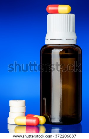 Cough syrup, glass bottle with a yellow-red pill and round tablets on glass with a blue background, nobody. - stock photo