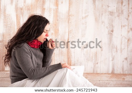Coughing beauty. Side view image of young sick woman with scarf on her neck sitting in bed and coughing with her country house on the background - stock photo