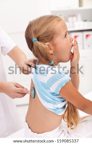 Coughing little girl at the doctor - respiratory system diseases in childhood - stock photo