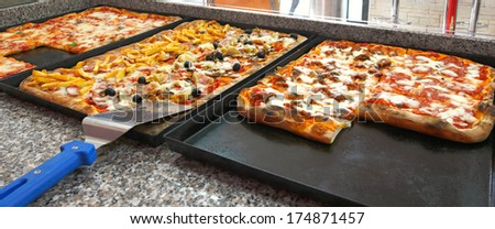 Counter of the pizzeria with trays and square pieces of pizza. - stock photo