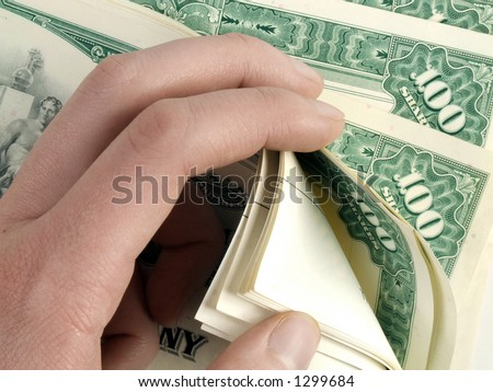 Counting hundreds of share certificates for a global company. - stock photo
