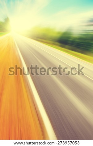 Country asphalt road in motion blur at sunset. - stock photo