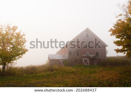 Country barn on a foggy morning during autumn, Stowe, Vermont, USA. - stock photo