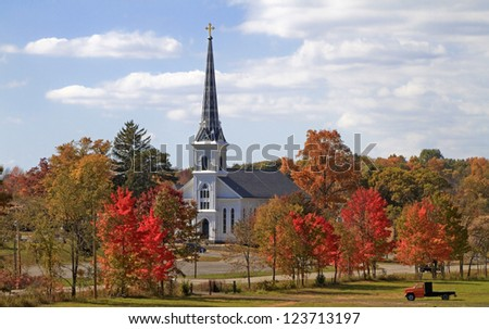 Country Church -- A small Catholic Church stands amid the changing colors of the trees -- Parnell, Michigan. - stock photo