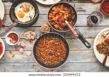 Country dinner tabletop with slow cooked meal in three skillets. Organic , homemade, healthy meal concept. Rustic style from above .  - stock photo