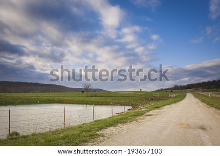 Country dirt road with pond and big blue sky with clouds. - stock photo