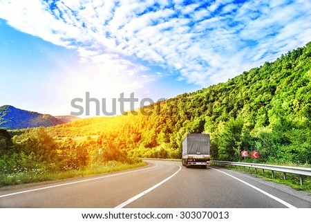 Country highway and a truck at sunset. - stock photo