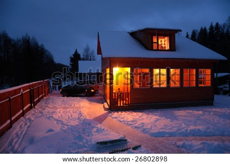 Country house in winter evening - stock photo
