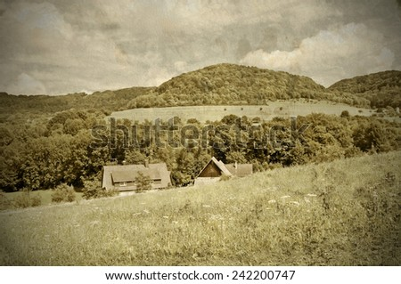 country idyll with old farmhouse and hill - stock photo
