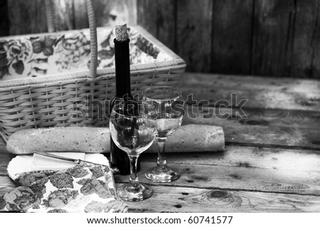 Country picnic for two with wine, bread and cheese, desaturated. - stock photo